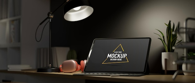 Espaço de trabalho na luz do quarto escuro do abajur de mesa tablet de tela em branco com fone de ouvido e decoração