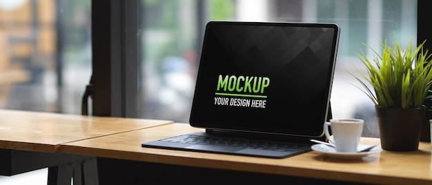 Espaço de trabalho portátil com maquete de tablet e xícara de café