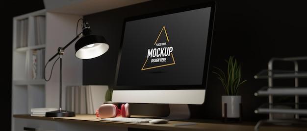 Espaço escuro para trabalho em casa à meia-noite, monitor de computador com tela em branco e luz do abajur