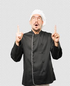 Espantado jovem chef apontando para cima com o dedo