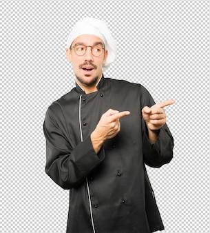 Espantado jovem chef apontando para você com o dedo