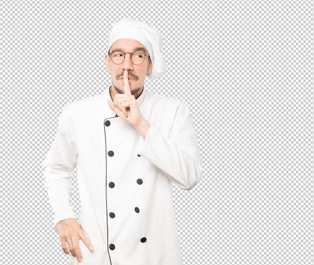 Espantado jovem chef pedindo silêncio gesticulando com o dedo