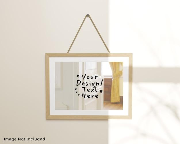 Espelho de reflexão com moldura de madeira pendurada na maquete de parede