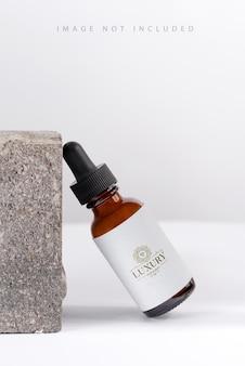 Essência de soro closeup em frasco de vidro de maquete em fundo de pedra óleo de cuidado de pele isolado