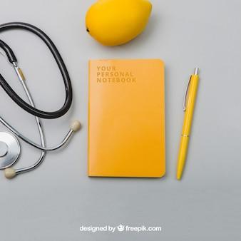 Estetoscópio, lemmon, caderno e caneta