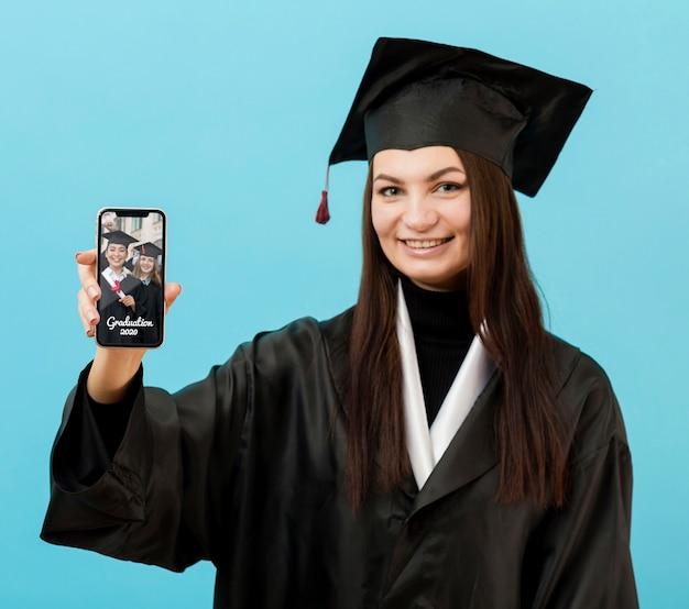 Estudante de graduação feliz segurando o telefone móvel