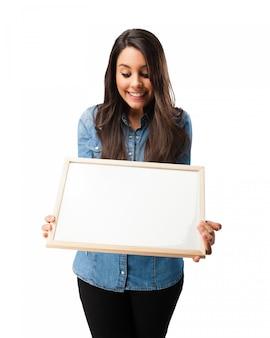 Estudante de sorriso que olha uma placa em branco