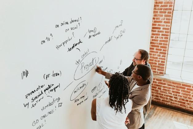 Executivos escrevendo em uma maquete de quadro branco