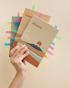 Feche a mão segurando a maquete de livros