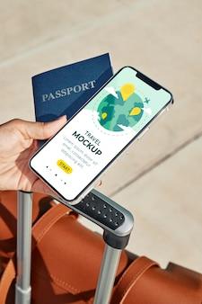 Feche a mão segurando o passaporte e o smartphone