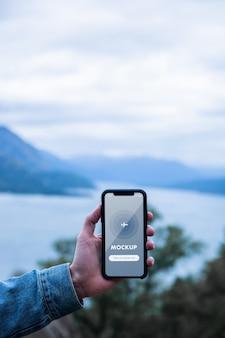 Feche a maquete de uma mão segurando um telefone celular no fundo das montanhas