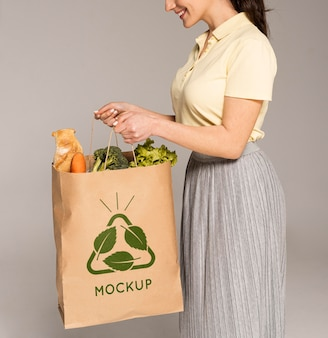 Feche a mulher segurando uma sacola com legumes