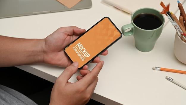 Feche nas mãos usando a maquete do smartphone na área de trabalho