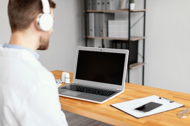 Feche o médico com laptop e fones de ouvido