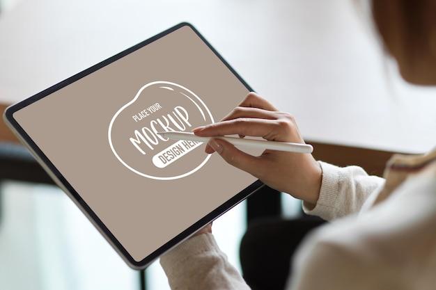 Feche uma mulher de negócios usando um tablet com uma caneta stylus