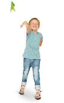 Felicidade garotinho sorrindo e voando retrato de estúdio de avião de papel