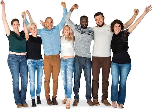 Felicidade grupo de pessoas amontoados e braços levantados sorrindo juntos