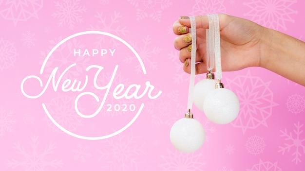 Feliz ano novo 2020 com bola de natal branca em fundo rosa