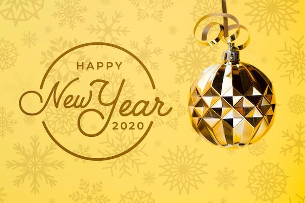 Feliz ano novo 2020 com bola de natal dourada sobre fundo amarelo