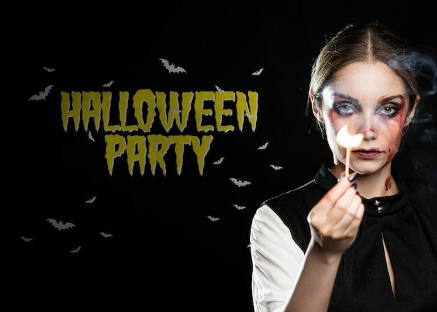 Feliz festa de halloween com garota de maquiagem segurando um fósforo