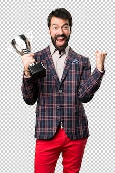 Feliz homem bem vestido segurando um troféu