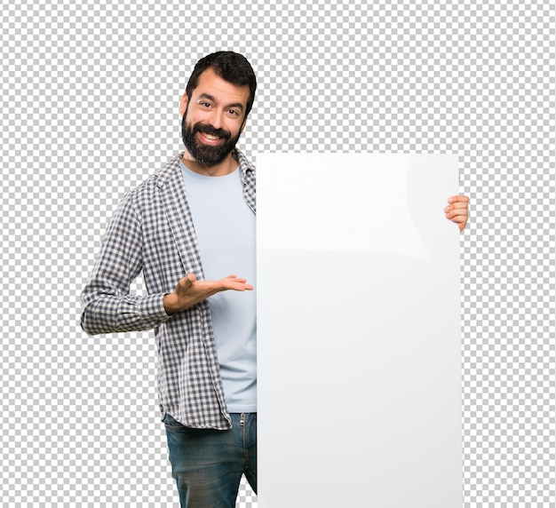 Feliz homem bonito com barba segurando um cartaz vazio