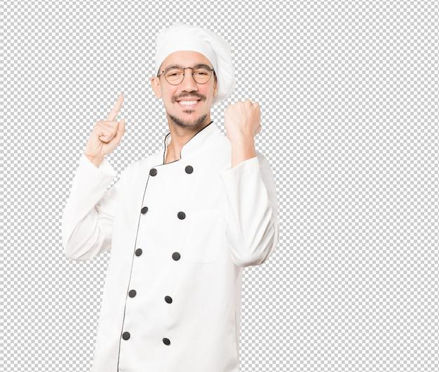 Feliz jovem chef fazendo um gesto competitivo