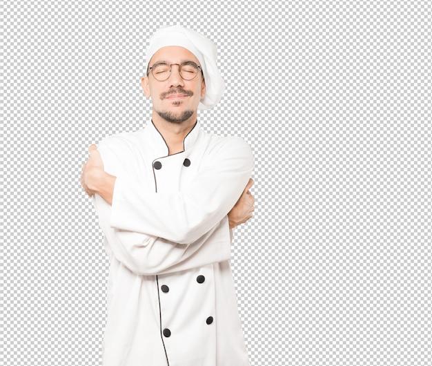 Feliz jovem chef fazendo um gesto de abraço