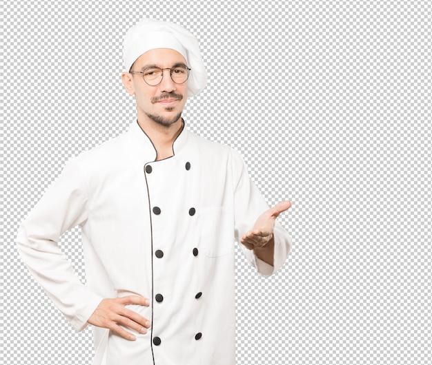 Feliz jovem chef fazendo um gesto de boas-vindas com a mão