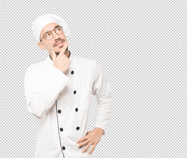 Feliz jovem chef fazendo um gesto de dúvida