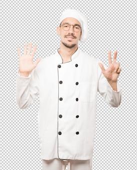Feliz jovem chef fazendo um gesto de número oito com as mãos
