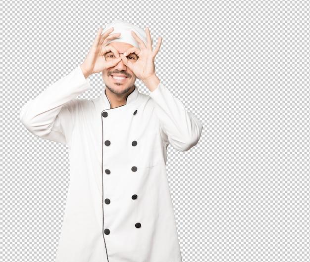 Feliz jovem chef usando as mãos como um binóculo