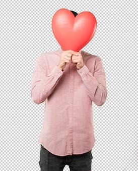 Feliz jovem segurando um coração grande brinquedo e fazendo gestos sobre o dia dos namorados