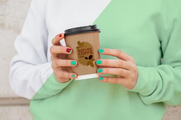 Fêmea de close-up com capuz bebendo café