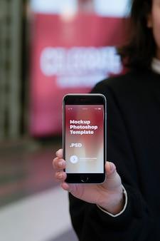 Fêmea leva smartphone moderno na mão direita
