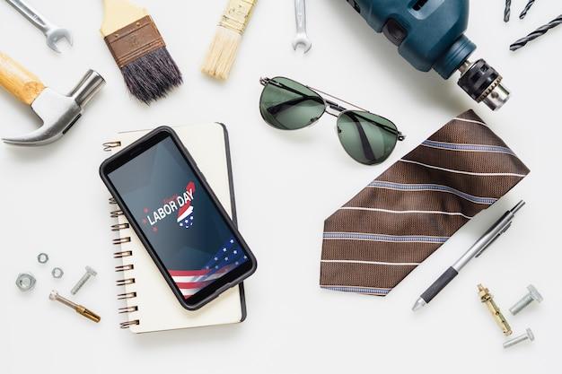 Flat lay mock up telefone inteligente com feliz dia do trabalho eua holiday e ferramentas essenciais de trabalhador
