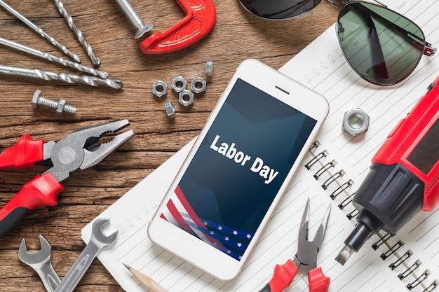 Flat lay mock up telefone inteligente com feriado do dia do trabalho eua e ferramentas essenciais de construção