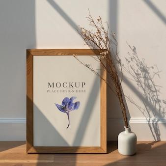 Flor de estática branca seca em um vaso branco por uma maquete de moldura de madeira em um piso de madeira