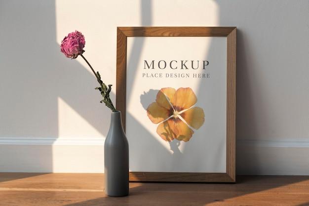 Flor de peônia rosa seca em um vaso cinza ao lado de uma maquete de madeira no chão