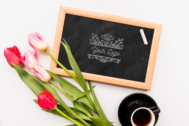 Flores na lousa e xícara de café