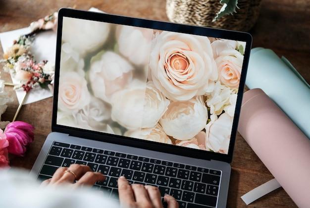 Florista usando uma maquete de tela de laptop floral