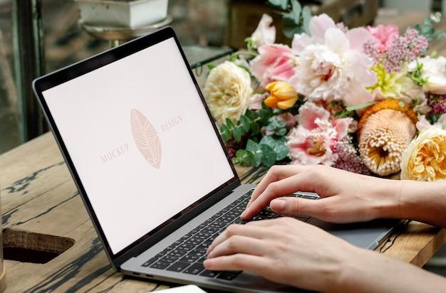 Florista usando uma maquete de tela de laptop