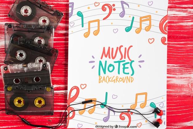 Folha com desenho de notas musicais e fitas ao lado
