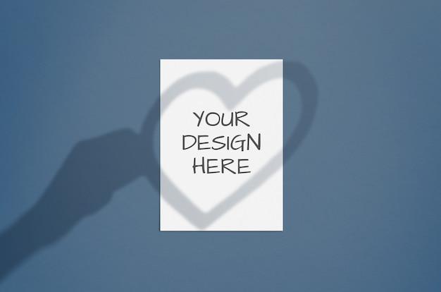 Folha de papel vertical branca em branco com sobreposição de sombra mão e coração. cartão de dia dos namorados moderno e elegante ou convite de casamento simulado
