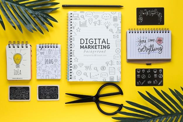 Folhas de notebooks e tesoura na mesa amarela
