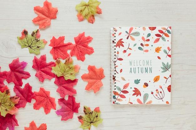 Folhas-de-rosa e verdes com o bloco de notas