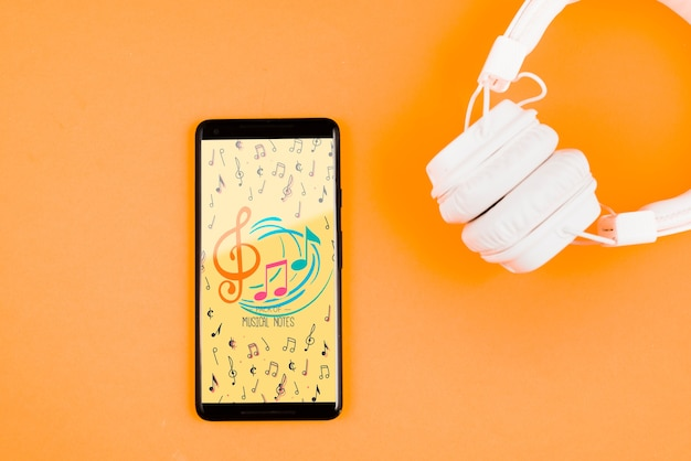 Fones de ouvido mock-up ao lado do celular