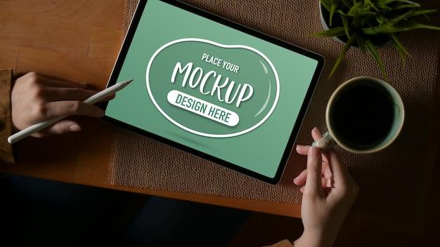 Foto aérea de mulher trabalhando com simulação de tablet e segurando a xícara de café na mesa de madeira