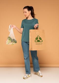 Foto completa de mulher segurando um saco de papel