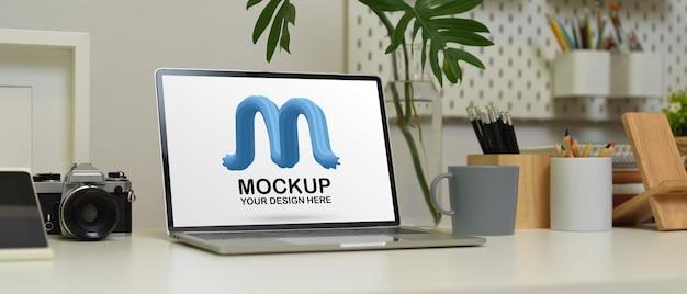 Foto recortada de espaço de trabalho com simulação de laptop, câmera, artigos de papelaria e decorações na mesa branca